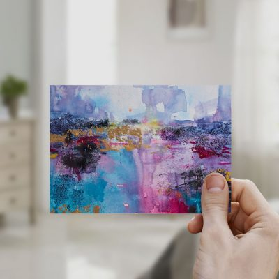 Hand holding a mini print in a bedroom
